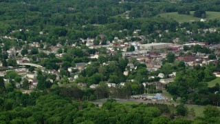 AX107_116 - 5K stock footage aerial video of small town among trees, East Palestine, Ohio