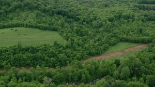 AX107_122 - 5K stock footage aerial video flying away from forests to reveal rural homes, Darlington, Pennsylvania