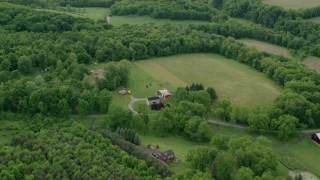 AX107_123 - 5K stock footage aerial video flying away from rural homes and forests, Darlington, Pennsylvania