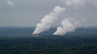 AX107_125 - 5K stock footage aerial video of steam from a power station's cooling towers, Beaver Valley Power Station, Pennsylvania