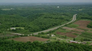 AX107_128 - 5K stock footage aerial video of an interstate bordered by forests and farmland, Beaver Falls, Pennsylvania