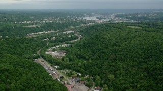 AX107_130 - 5K stock footage aerial video of forests and industrial buildings, Beaver Falls, Pennsylvania
