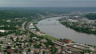 AX107_135 - 5K stock footage aerial video of a bridge spanning a river along a town, Monaca, Ohio River, Pennsylvania