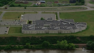 AX107_143 - 5K stock footage aerial video flying by Beaver County Jail along the water, Aliquippa