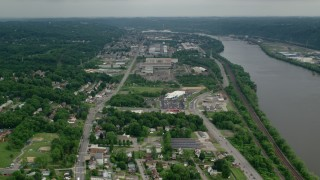 AX107_144 - 5K stock footage aerial video approaching small factories along a river, Ambridge, Pennsylvania