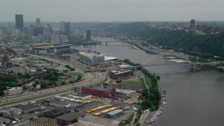 AX107_169 - 5K stock footage aerial video of skyscrapers and football stadium while approaching bridge, Downtown Pittsburgh, Pennsylvania