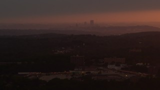 AX108_003 - 4K stock footage aerial video flying by apartment buildings, Penn Hills, Downtown Pittsburgh, sunset