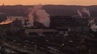 AX108_019 - 4K stock footage aerial video of U.S. Steel Mon Valley Works and smoke stacks, Braddock, Pennsylvania, sunset