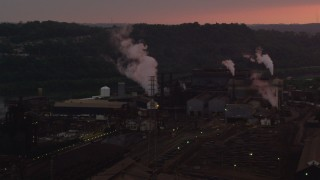 AX108_024 - 4K stock footage aerial video passing buildings at the U.S. Steel Mon Valley Works, Braddock, Pennsylvania, sunset
