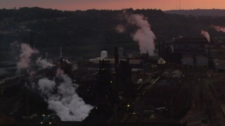 AX108_025 - 4K stock footage aerial video passing by buildings at the U.S. Steel Mon Valley Works, Braddock, Pennsylvania, sunset