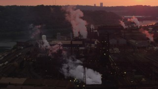 AX108_026 - 4K stock footage aerial video of smoke rising from the U.S. Steel Mon Valley Works, Braddock, Pennsylvania, sunset