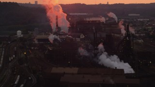 AX108_027 - 4K stock footage aerial video of smoke rising from the U.S. Steel Mon Valley Works, Braddock, Pennsylvania, sunset