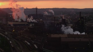 AX108_028 - 4K stock footage aerial video of smoke rising from the U.S. Steel Mon Valley Works, Braddock, Pennsylvania, sunset