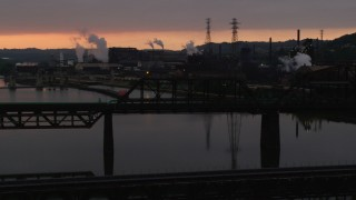 AX108_031 - 4K stock footage aerial video of U.S. Steel Mon Valley Works viewed from a bridge, Braddock, Pennsylvania, sunset
