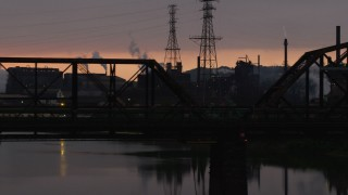AX108_033 - 4K stock footage aerial video of U.S. Steel Mon Valley Works seen through a bridge, Braddock, Pennsylvania, sunset