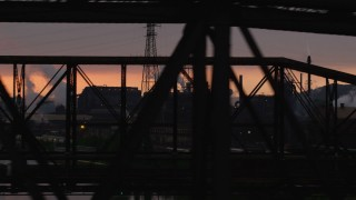 AX108_034 - 4K stock footage aerial video of U.S. Steel Mon Valley Works seen through a bridge, Braddock, Pennsylvania, sunset
