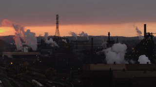 AX108_035 - 4K stock footage aerial video of rising smoke from the U.S. Steel Mon Valley Works, Braddock, Pennsylvania, sunset