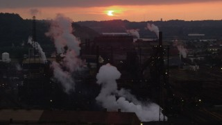 AX108_036 - 4K stock footage aerial video of rising smoke from the U.S. Steel Mon Valley Works, Braddock, Pennsylvania, sunset