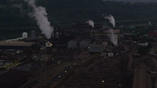 AX108_038 - 4K stock footage aerial video of smoke rising from the U.S. Steel Mon Valley Works, Braddock, Pennsylvania, twilight