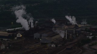 AX108_039 - 4K stock footage aerial video passing a building at the U.S. Steel Mon Valley Works, Braddock, Pennsylvania, twilight