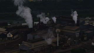 AX108_040 - 4K stock footage aerial video passing a building at the U.S. Steel Mon Valley Works, Braddock, Pennsylvania, twilight