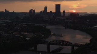 AX108_052 - 4K stock footage aerial video of Downtown Pittsburgh skyline seen from the Monongahela River, Pennsylvania, sunset
