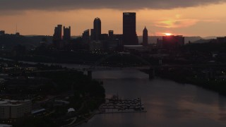 AX108_053 - 4K stock footage aerial video of Downtown Pittsburgh skyline seen from the Monongahela River, Pennsylvania, sunset