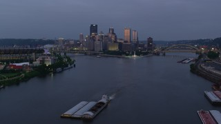 AX108_095 - 4K stock footage aerial video flying over Ohio River toward Downtown Pittsburgh, Pennsylvania, twilight