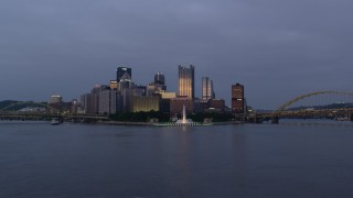 AX108_097 - 4K stock footage aerial video of a low approach toward Point State Park and Downtown Pittsburgh, Pennsylvania, twilight