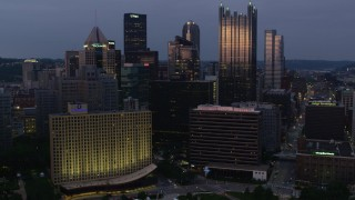AX108_099 - 4K stock footage aerial video flying over Downtown Pittsburgh buildings, Pennsylvania, twilight