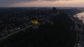 AX108_103 - 4K stock footage aerial video of St. Mary of the Mount Church and suburban neighborhoods, Pittsburgh, Pennsylvania, twilight