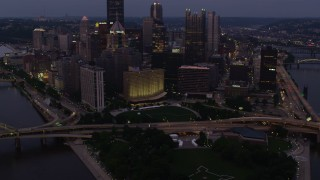 AX108_112 - 4K stock footage aerial video flying by Downtown Pittsburgh skyscrapers and office buildings, Pennsylvania, twilight