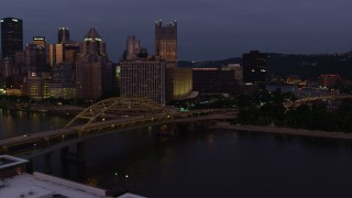 AX108_122 - 4K stock footage aerial video flying by Downtown Pittsburgh skyscrapers revealing Point State Park, Pennsylvania, twilight