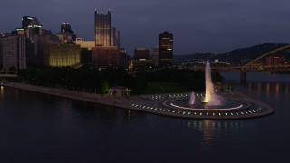 AX108_123 - 4K stock footage aerial video flying by Point State Park Fountain, Downtown Pittsburgh, Pennsylvania, twilight