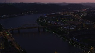 AX108_143 - 4K stock footage aerial video of Heinz Field from the Allegheny River, Pittsburgh, Pennsylvania, twilight