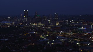 AX108_156 - 4K stock footage aerial video approaching Heinz Field and skyscrapers, Downtown Pittsburgh, Pennsylvania, night