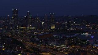 AX108_158 - 4K stock footage aerial video approaching Downtown Pittsburgh while flying by Heinz Field, night