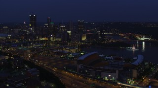 AX108_160 - 4K stock footage aerial video flying toward Downtown Pittsburgh passing Heinz Field, Pennsylvania, night
