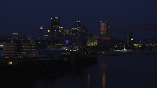 AX108_164 - 4K stock footage aerial video of Downtown Pittsburgh skyscrapers from West End Bridge, Pennsylvania, night