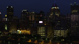 AX108_171 - 4K stock footage aerial video flying by skyscrapers and tilt down on Byham Theater, Downtown Pittsburgh, night