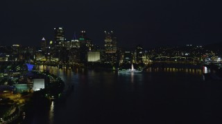 AX108_217 - 4K stock footage aerial video descending toward river by Point State Park, Downtown Pittsburgh, night