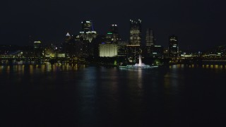 AX108_218 - 4K stock footage aerial video of a low approach toward Point State Park, Downtown Pittsburgh, night