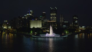 AX108_219 - 4K stock footage aerial video flying over Point State Park toward skyscrapers, Downtown Pittsburgh, night