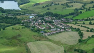 AX109_003 - 6K stock footage aerial video of rural homes surrounded by green, Banton, Scotland