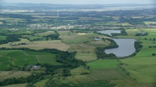AX109_004 - 6K stock footage aerial video of green farms and a reservoir, Denny, Scotland