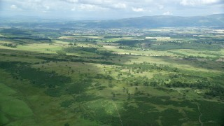 AX109_006 - 6K stock footage aerial video of approach green farmland and rural landscape, Stirling, Scotland
