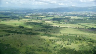 AX109_007 - 6K stock footage aerial video approach farms in a green rural landscape, Stirling, Scotland