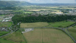 AX109_018 - 6K stock footage aerial video of a reverse view of Stirling Castle, neighborhoods, and farmland, Scotland