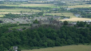 AX109_019 - 6K stock footage aerial video of hilltop Stirling Castle among trees, Scotland