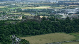 AX109_020 - 6K stock footage aerial video of Stirling Castle atop a tree-covered hill in Scotland